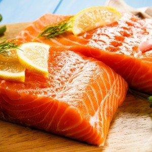 Fresh raw sockeye salmon fillets on cutting board.